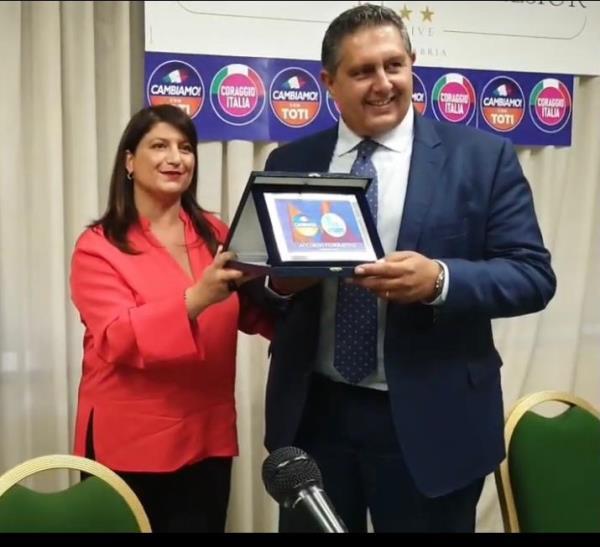 """images La presidente di """"Insieme per il Meridione"""", Tiziana Demma, sigla l'accordo con """"Cambiamo con Toti"""" consegnando un'opera del maestro Rizzi"""